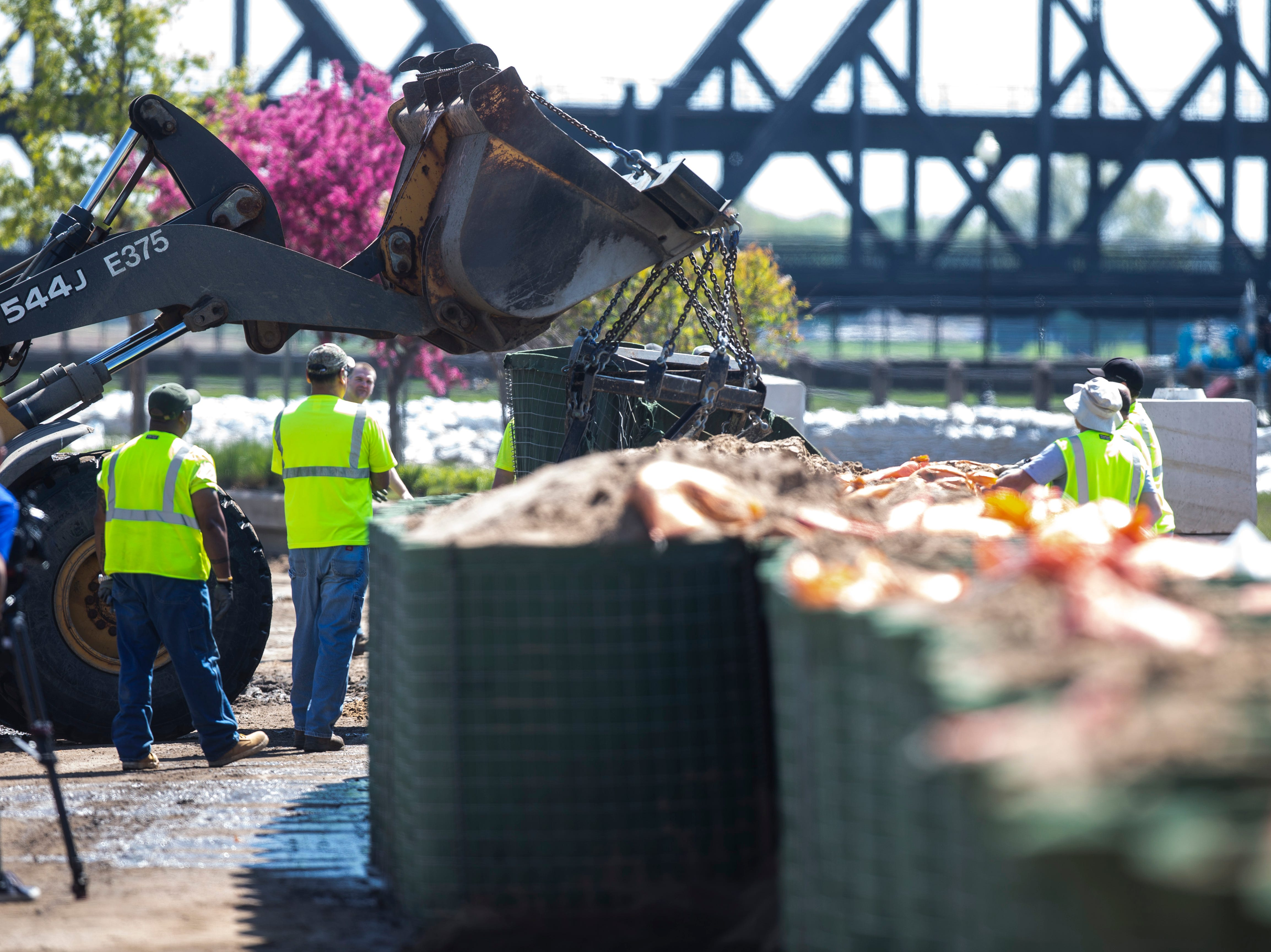 City of Davenport workers being to remove a HESCO barrier along Front Street which was impacted by floodwaters, Wednesday, May 15, 2019, in downtown Davenport, Iowa.