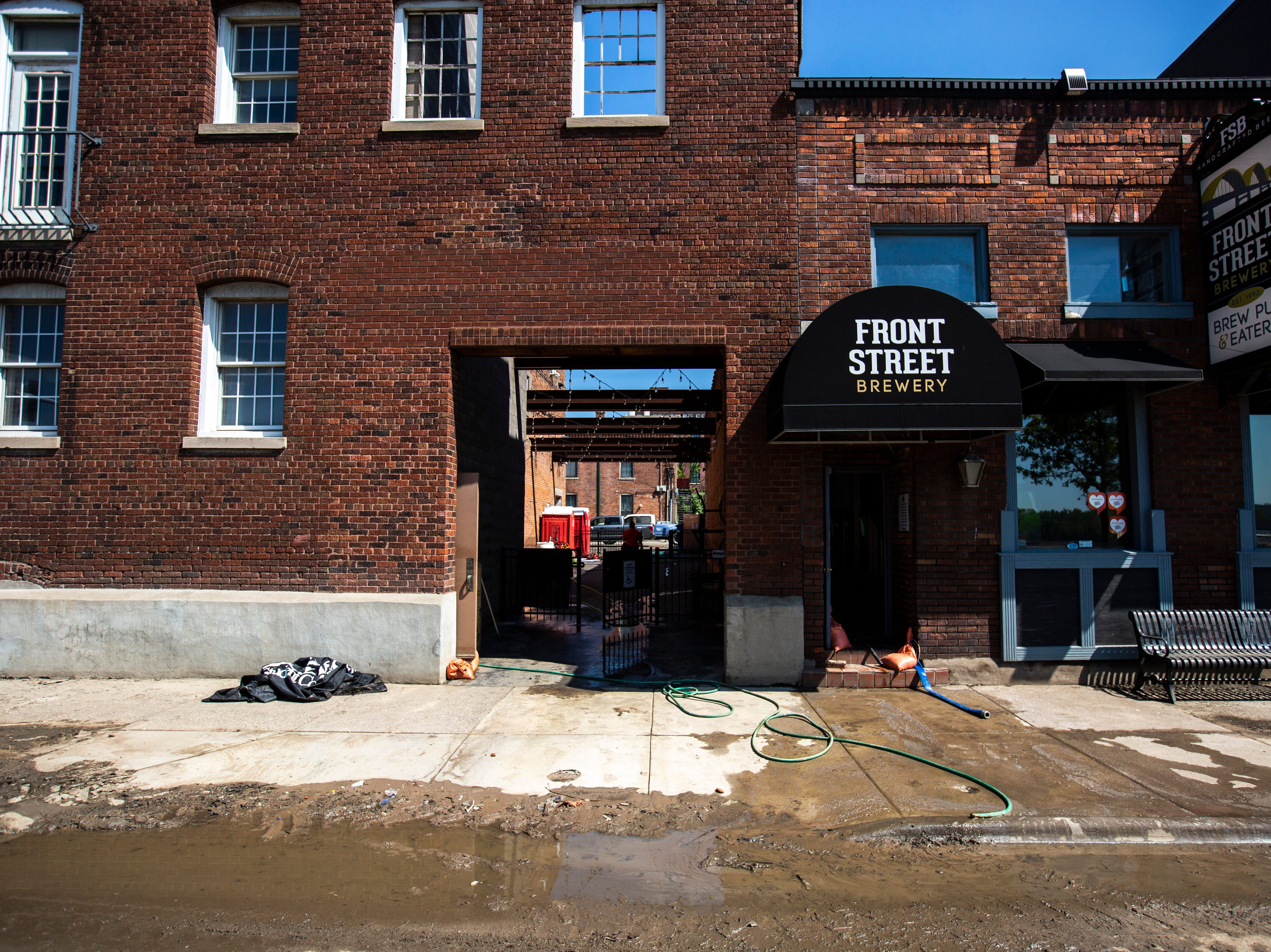 Mud mixes with clean water outside of Front Street Brewery as cleanup begins after floodwaters receded, Wednesday, May 15, 2019, in downtown Davenport, Iowa.