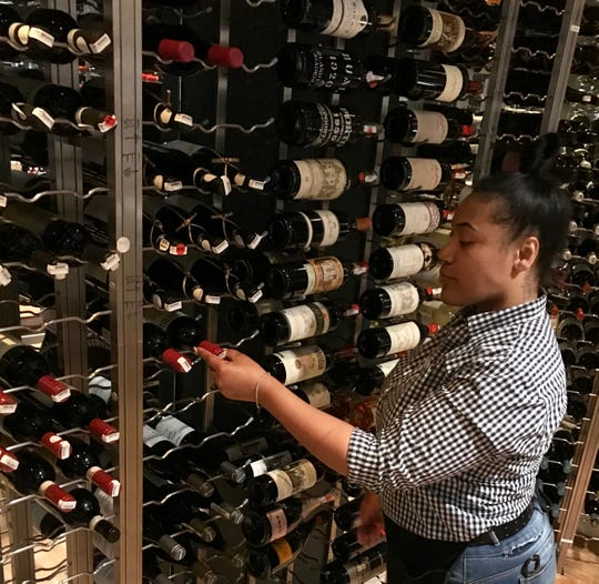 Amber Woods of Clinton, an employee at CAET in Ridgeland, pulls a bottle of wine from the restaurant's wine room.
