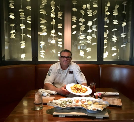 Chef/owner Derek Emerson  of CAET sits in a booth decorated with moon wind chimes from McCarty Pottery in Merigold.