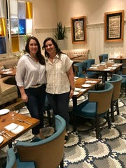 Jennifer Emerson and Effie Hubanks, who with Derek Emerson own CAET, show off the main dining room, which has been refreshed.
