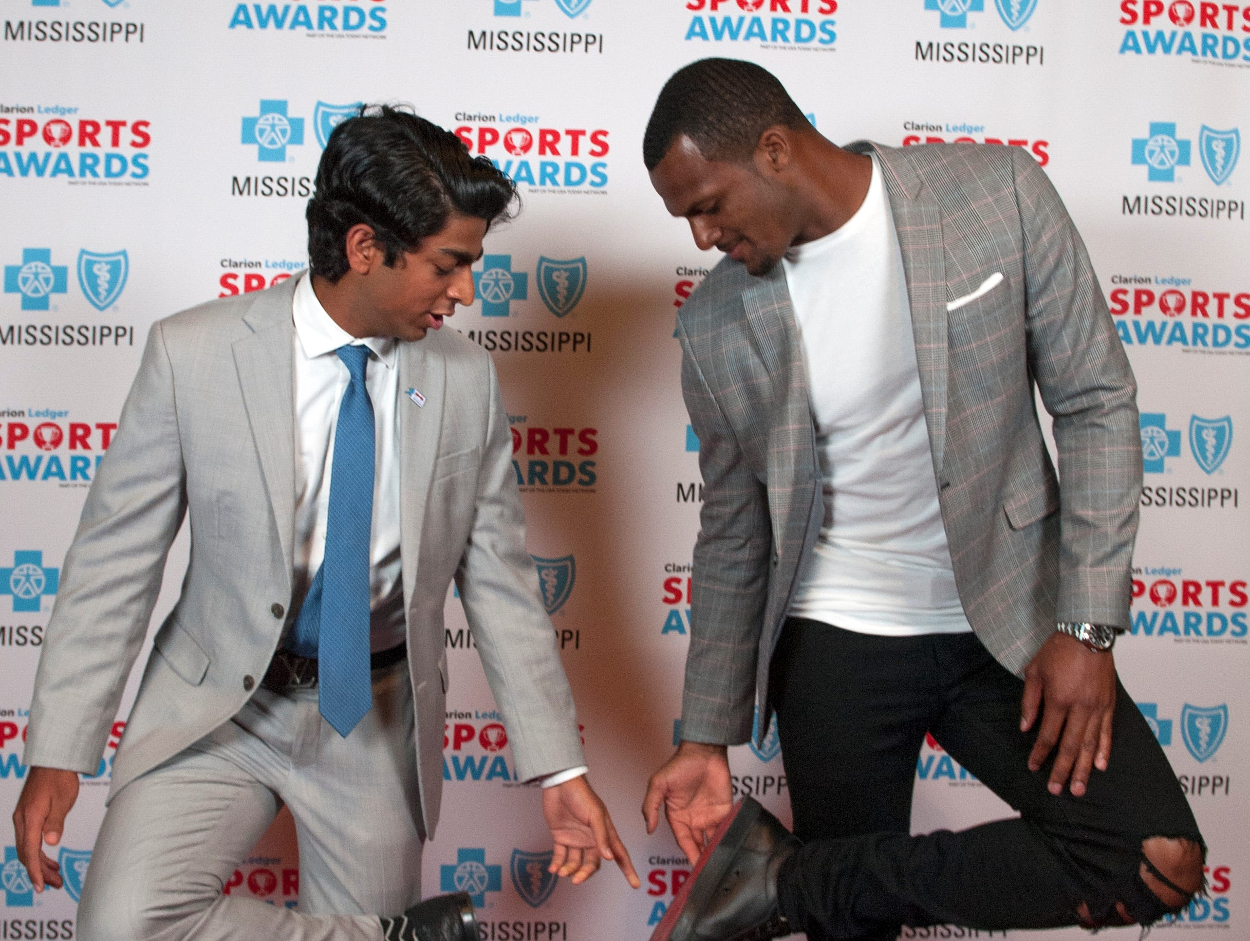 Houston Texans quarterback Deshaun Watson lifts his shoe to compare when Wendy's High School National Heisman Award Winner Sunjay Chawla asks about what he's wearing during their meeting at the Clarion Ledger High School Sports Awards Tuesday. Chawla is from Pillow Academy in Greenwood.