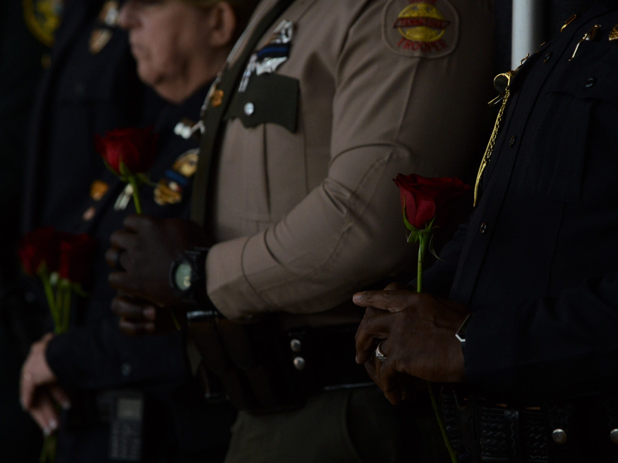 Law enforcement officers from throughout West Tennessee hold roses for their fallen brothers and sisters in blue at the Carl Perkins Civic Center in Jackson during the National Law Enforcement Memorial Service on Wednesday, May 15, 2019.