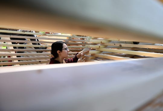 Union University senior Christen Harper sands down plywood inside a 3D church sculpture at the school. The sculpture was built to show solidarity for churches burned around the world.