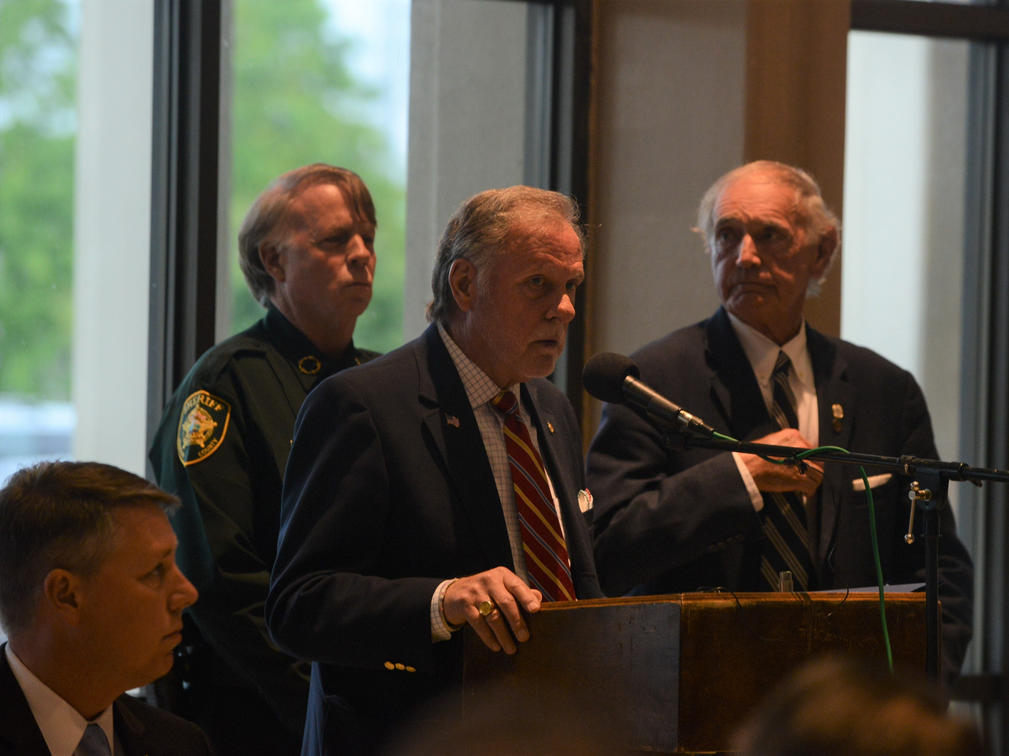 Madison County Mayor Jimmy Harris speaks flanked by Jackson City Mayor Jerry Gist and Madison County Sheriff John Mehr at the Carl Perkins Civic Center in Jackson during the National Law Enforcement Memorial Service on Wednesday, May 15, 2019.