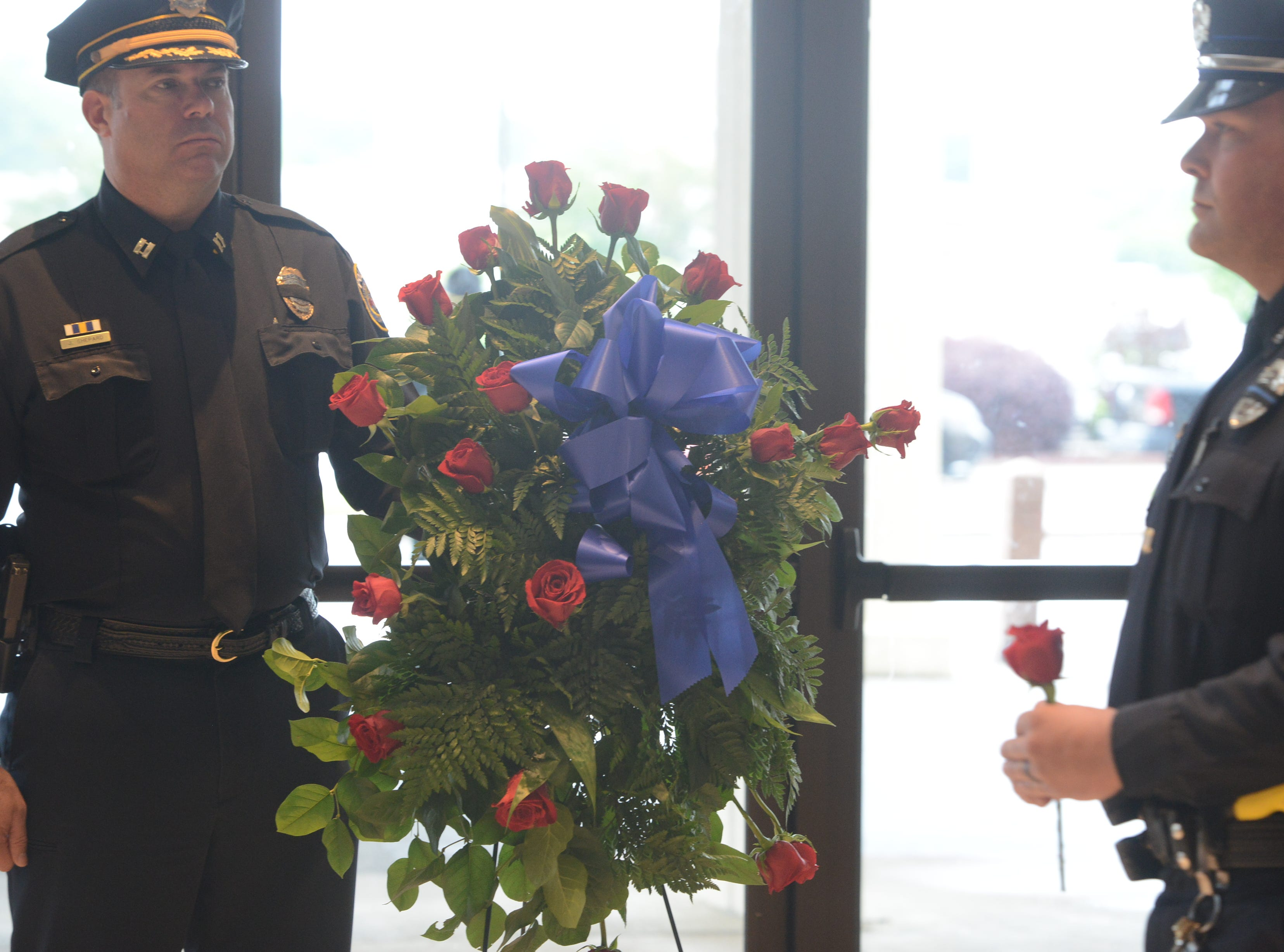 Jackson Police Department Captain Jeff Shepard stands at attention as fellow officers place roses in a wreath in memory of fallen public servants at the National Law Enforcement Memorial Service at the Carl Perkins Civic Center in Jackson on Wednesday, May 15, 2019.