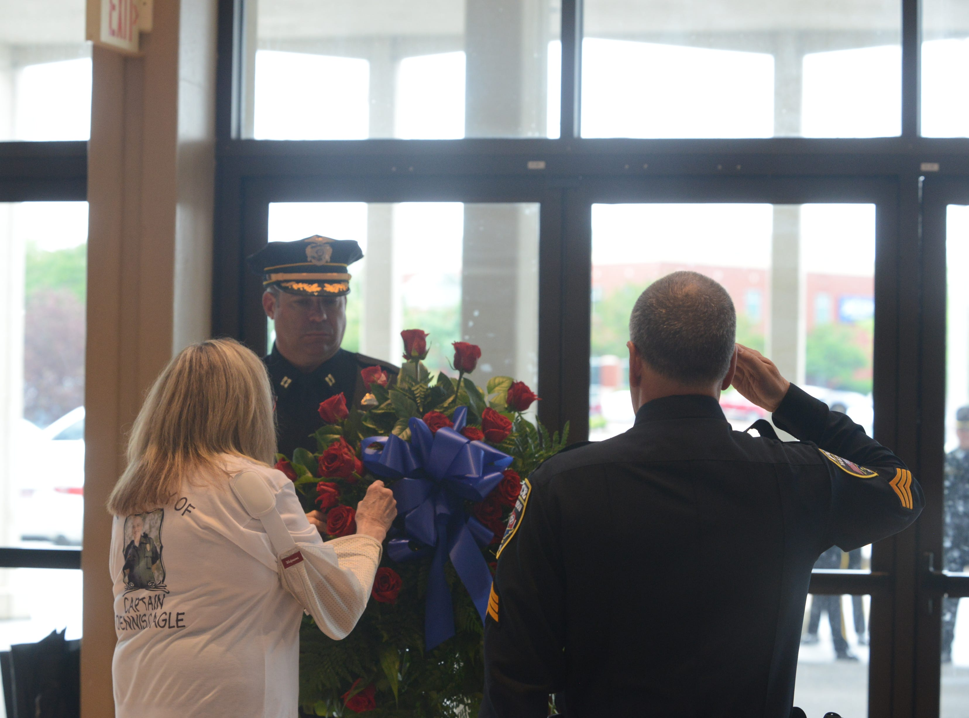 Judy Cagle Deberry places a rose in commemorative wreath to honor her late husband, Captain Dennis Cagle of the Henderson Police Department, during the National Law Enforcement Memorial Service at the Carl Perkins Civic Center in Jackson on Wednesday, May 15, 2019.