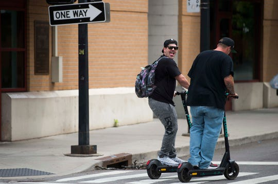 Scooter riders traverse downtown Knoxville, Wednesday, May 15, 2019.