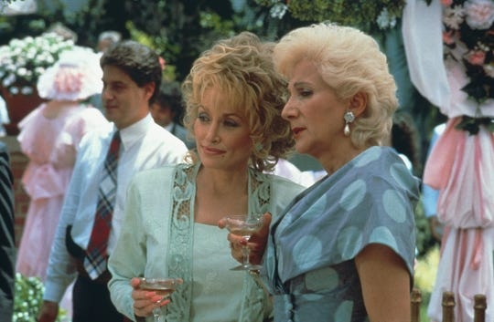 "Truvy (Dolly Parton, left) and Clairee (Olympia Dukakis) gossip during a scene in ""Steel Magnolias."""
