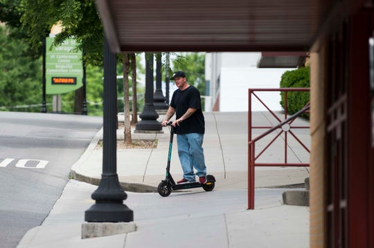A scooter rider passes the Locust Street parking garage in downtown Knoxville, Wednesday, May 15, 2019.