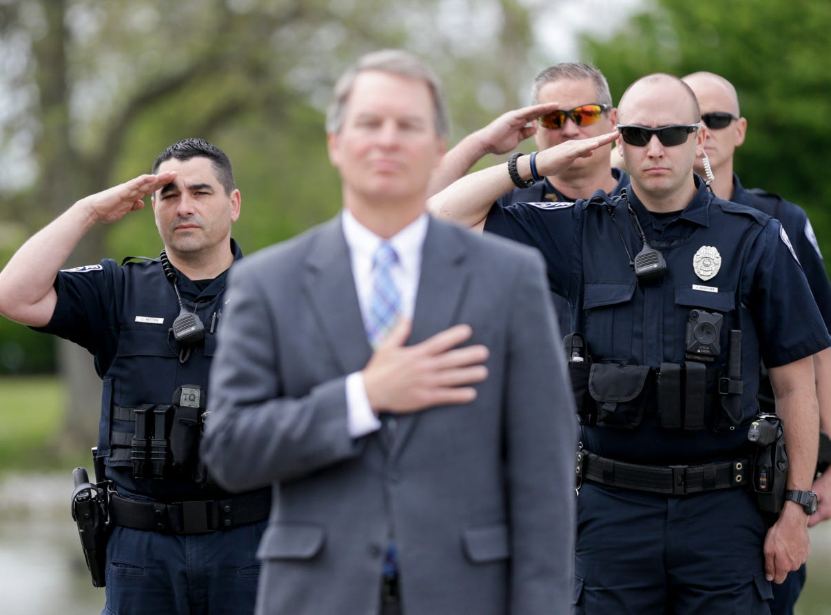 Members of the public and local law enforcement stand during the presentation of colors during from the annual police memorial, Wednesday, May 15, 2019, at Columbian Park in Lafayette.