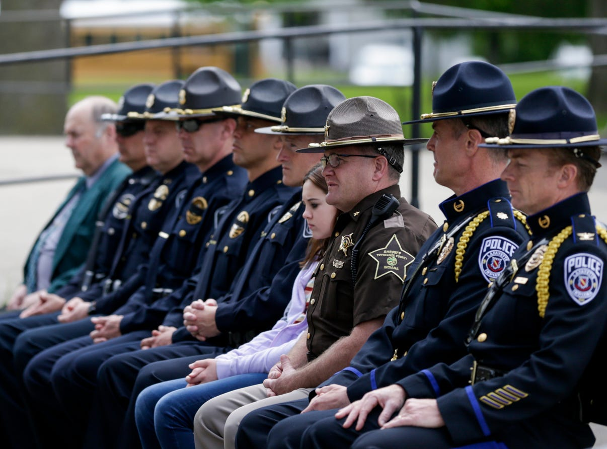 Members of law enforcement sit during the annual police memorial, Wednesday, May 15, 2019, at Columbian Park in Lafayette.