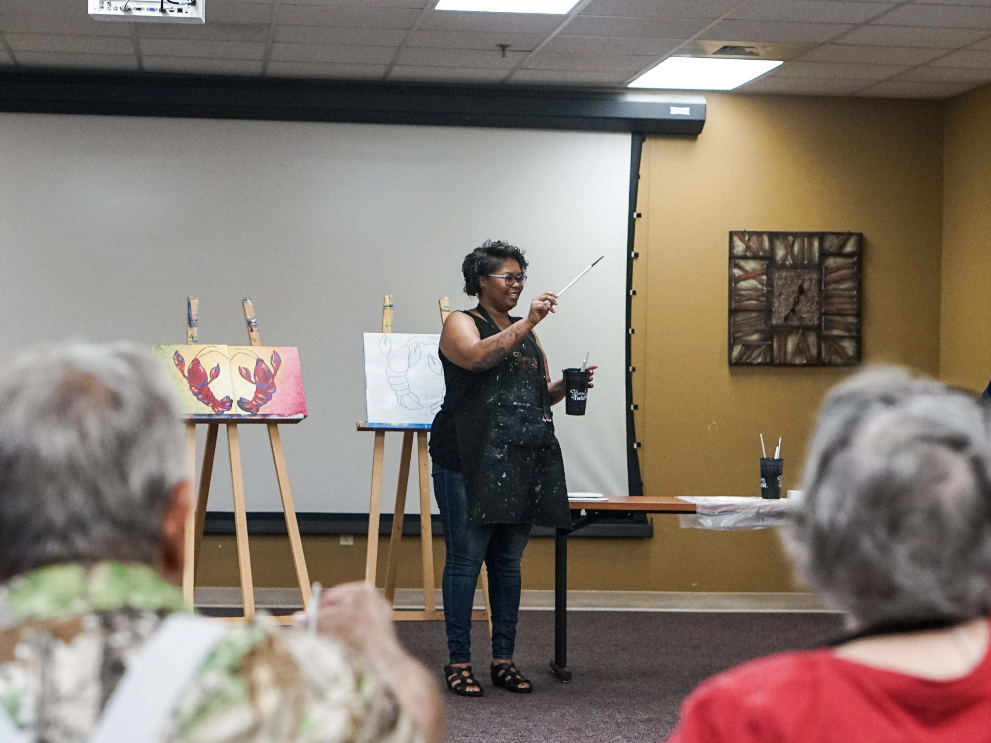 Former stroke patients who are members of Lafayette General Medical Center's Acadiana Stroke Support Group celebrated their recovery by painting a crawfish portrait in conjunction with Painting with a Twist and help from local artist Deondra Martin May 14.
