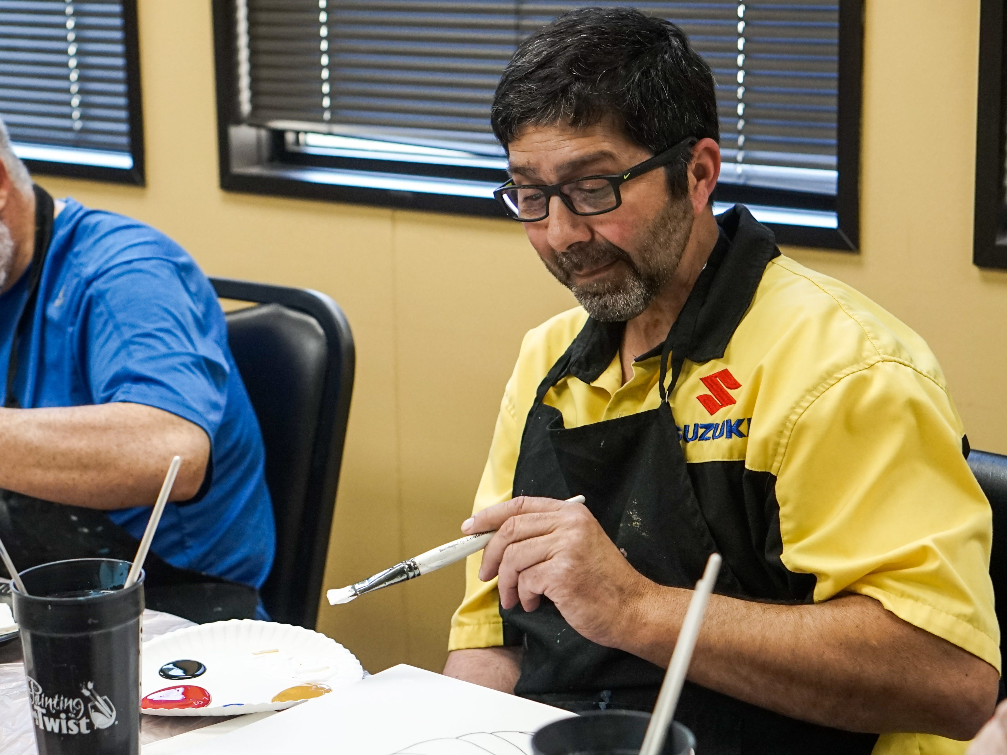 Former stroke patient Randy Young paints at an event in conjunction with Painting with a Twist Tuesday, May 14.
