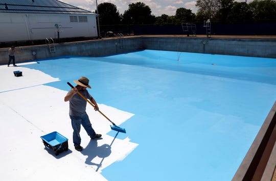 Lancaster Parks and Recreation employees Matt Conrad, left, and Brent Siders paint the bottom of Miller Pool Wednesday, May 15, 2019, in Lancaster. Parks and Recreation department employees have spent the last few weeks preparing the city's two outdoor pools for the summer season. Tiki Pool will open for Memorial Day weekend. Miller and Tiki pools will open full time on June 1.