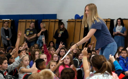 """Madison Ross, Lancaster Parks and Recreation's pool manager, hands a swimming pass to a Medill Elementary student Wednesday morning, May 15, 2019, in Lancaster. Ross accompanied Lancaster High School students to the elementary school to distribute passes. High school students sold more than 1,300 Krispy Kreme doughnuts to help offset the cost to the parks department for providing the passes. Eighty passes good for five visits were given to elementary students. Jessica Reiber, a guidance counselor at LHS, said she uses the program to help build leadership skills in high school students involved. She said the students who sell the doughnuts don't see any of the proceeds and it's all passed on to the younger students. """"We've got kids that want to give back and who better to partner with than the parks department,""""  Fairfield County Sheriff's Dep. Jeff Dixon, the LHS school resource officer, said. """"For some of [the high school students] it's really an opportunity to give back for the first time,"""" Dixon said."""