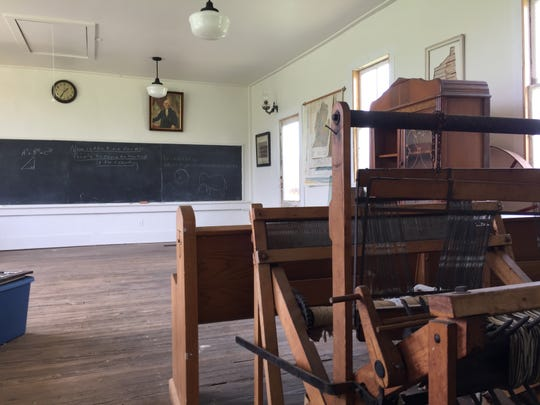An antique loom sits in the restored 1849 Hicks School at the Warner family farmstead in Brighton Township, Wednesday, May 15, 2019.