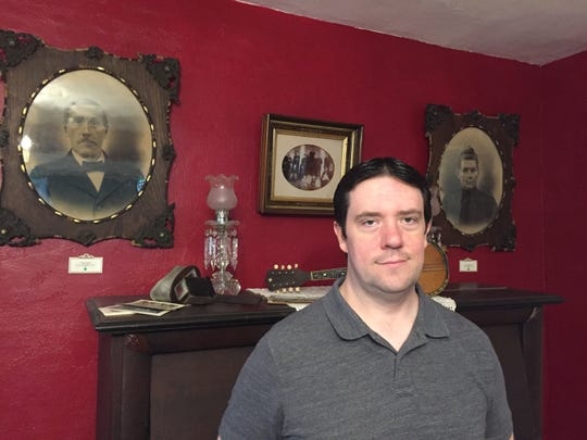 Tim Bennett stands between portraits of his third-great-grandparents Timothy and Lucretia Bennett in their 1855 farmhouse in Brighton Township, Wednesday, May 15, 2019.