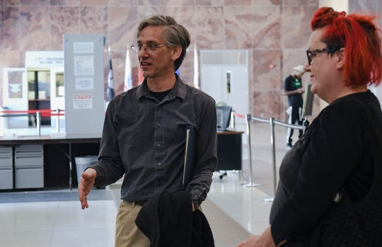 Martin Mashon and Julia Miller discuss their case in the lobby of Lansing City Hall May 15, 2019 after a jury found them innocent of trespassing at a CATA bus station but convicted Mashon of resisting arrest.