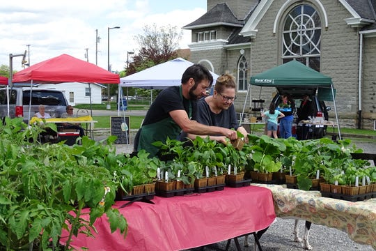Daniel Neef of Galion helps a customer during the Crestline Farmers' Market on Tuesday afternoon.