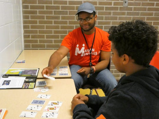 Trent Ramsey, who is studying English education at The Ohio State University, meets with fifth grader Xavion Ashburn at George Washington Elementary Wednesday afternoon. The duo meets once a week and they mostly play cards, talk about football and life after school.