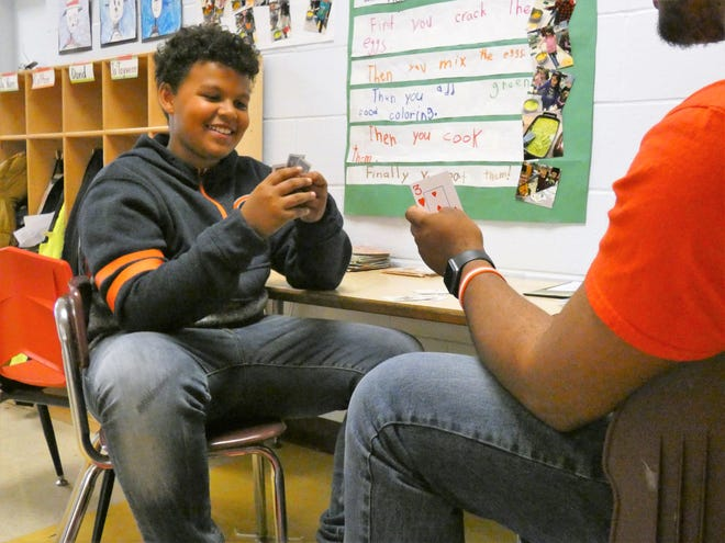 Xavion Ashburn, a fifth grader at George Washington Elementary, smiles during a game of Go Fish with his mentor Trent Ramsey during the lunch period Wednesday afternoon.