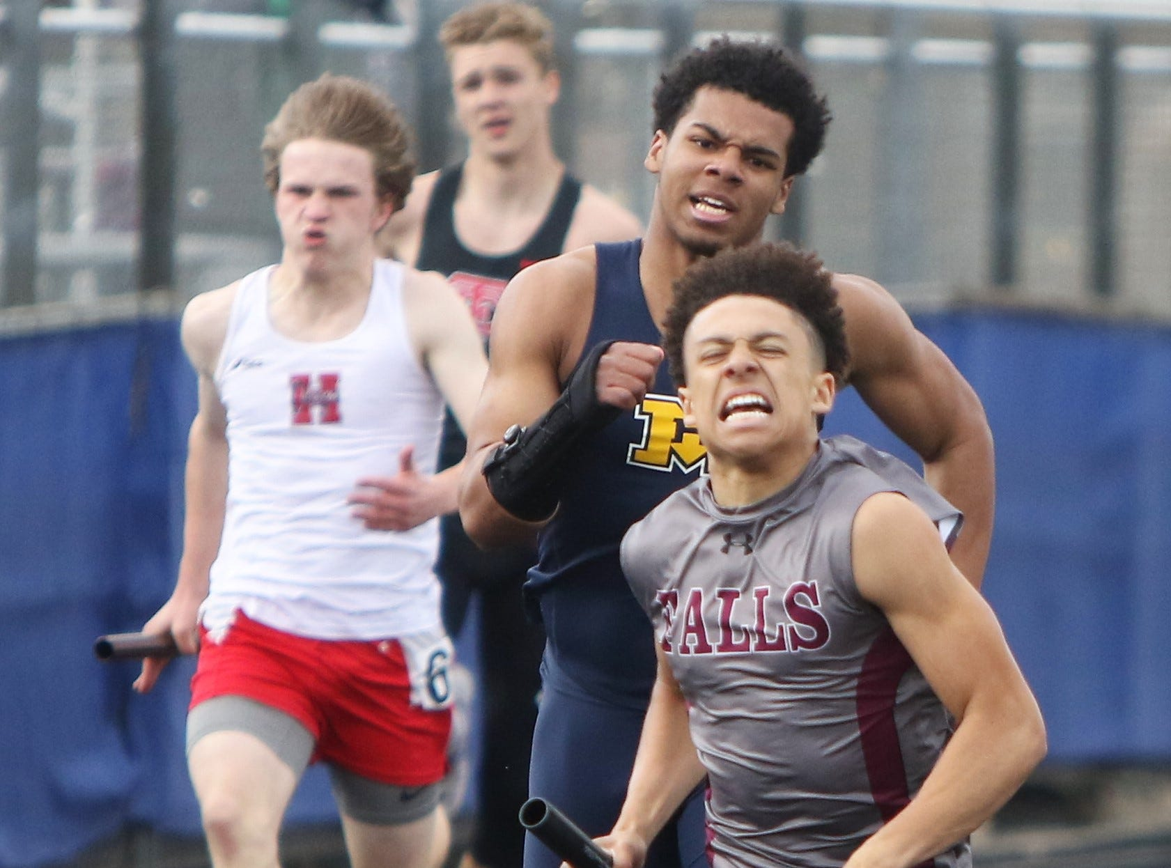 Quintin Redding of Menomonee Falls (right) holds off the pack, including Riley Nowakowski of Marquette, to win the 4x100 relay at the Greater Metro Conference outdoor championships on May 14, 2019.