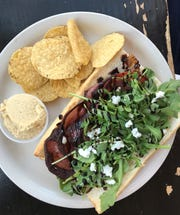 The National cafe in Walker's Point sears thin-sliced salami for its sandwich with goat cheese, arugula, fennel and balsamic vinegar.