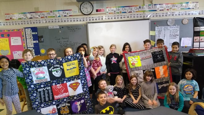 A second-grade class at Swanson Elementary School proudly holds up quilts made by Mary Felkner out of T-shirts the students donated. The Brookfield resident makes the quilts for local nursing homes and the VA.