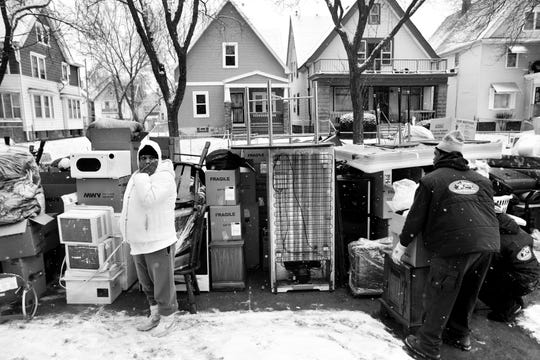 """Ara Sparkman looks over her belongings as they are placed on the sidewalk in front of the apartment she was just evicted from in Milwaukee. This image is included in """"Evicted,"""" an exhibit based on Matthew Desmond's book about evictions of low-income renters in Milwaukee. The exhibit is coming to Milwaukee's west side in June."""