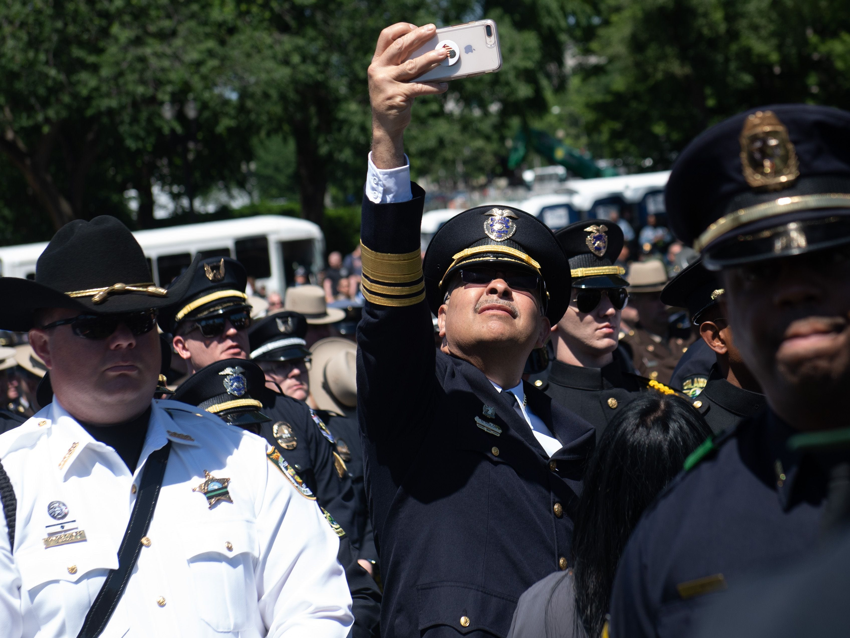A police officer uses his phone to take a photo during the 38th Annual National Peace Officers'  Memorial Service honoring law enforcement officers who were killed in the line of duty, at the US Capitol.