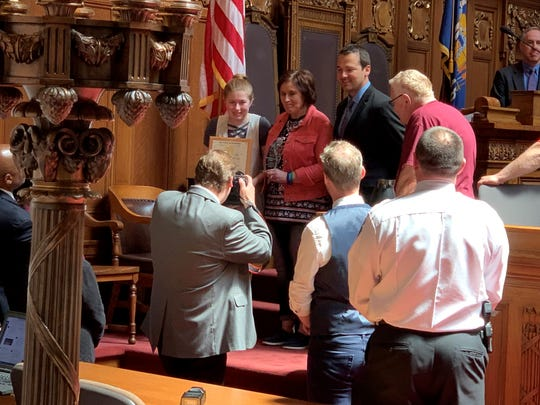 "Jayme Closs, who was kidnapped in October and held for 88 days by a man who killed her parents, accepts the ""hometown hero"" award from the Wisconsin Assembly."