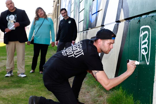 "Artist and designer David Mark Zimmerman, aka ""Bigshot Robot,"" signs the mural he created for the  Milwaukee Bucks at Brix parking structure in Walker's Point."