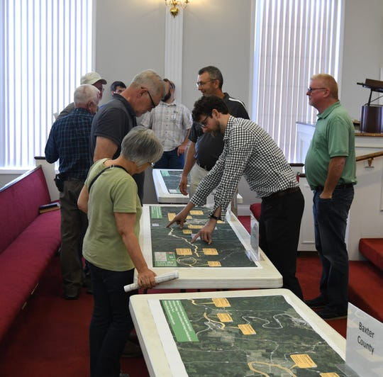 Visitors to the Arkansas Department of Transportation's public meeting on Highway 412 look at aerial maps of the highway Tuesday evening in Yellville.
