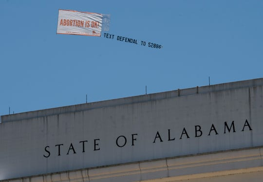 Legal abortion supporters fly a banner reading Abortion is OK near the Alabama State Capitol building in downtown Montgomery, Ala., on Wednesday May 15, 2019.
