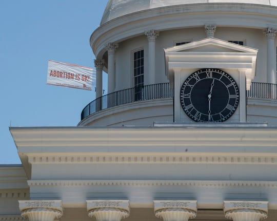 Un letrero que dice 'Aborto is OK' sobrevuela el capitolio en Alabama.