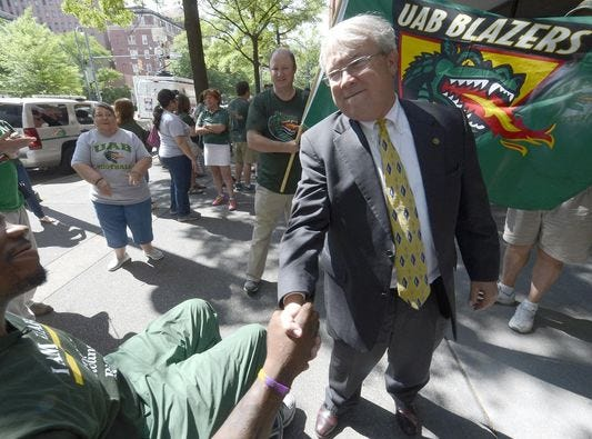 Rep. Jack Williams, right, shakes hands with Tim Alexander, a former football team member, outside the UAB Administration Building on June 1 in Birmingham.