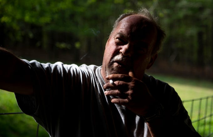 Larry Elmore smokes a cigarette as he breaks from working on Dr. Sam Barnes property Wednesday morning, April 17, 2019, in Cookeville, Tenn. Elmore first began taking opioids for legitimate pain from working in the mines. He did not know it was addictive at first until he was using the pills for everything.