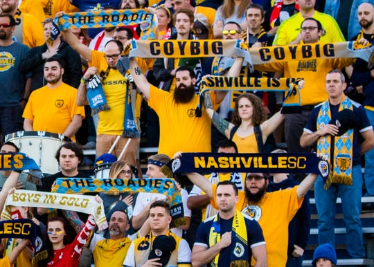 Fans hold Nashville SC scarves during the National Anthem before Nashville's 3-2 win over South Georgia Tormenta FC 2 at MTSU's Dean A. Hayes Track & Soccer Stadium on May 14, 2019.