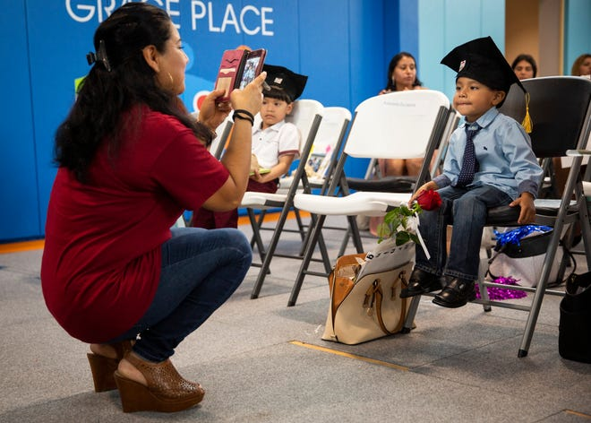 Adelaida Escalante takes a photo of her son Jarol Barron during the Bright Beginnings family literacy program graduation at Grace Place in Golden Gate on Wednesday, May 15, 2019.