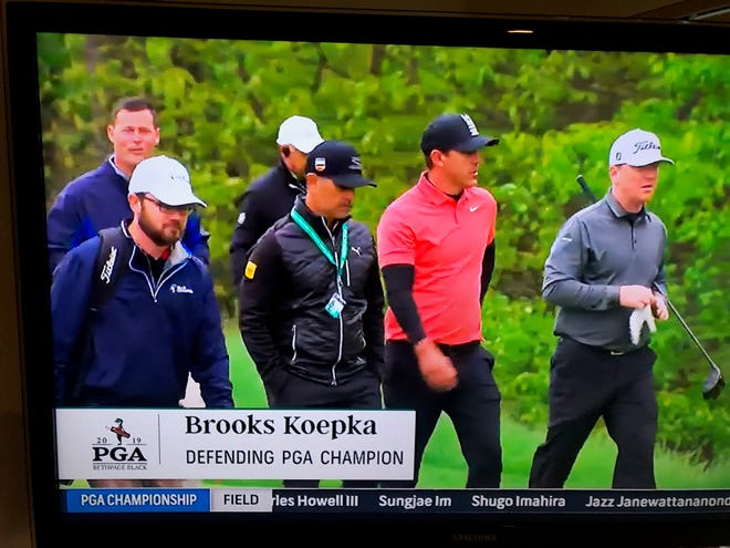 Hideout's Justin Bertsch (far right) walks with defending PGA Championship winner Brooks Koepka during a practice round for the PGA Championship at Bethpage Black on Tuesday. Bertsch's caddie, former Estero High and FGCU golfer David Steele, is far left.