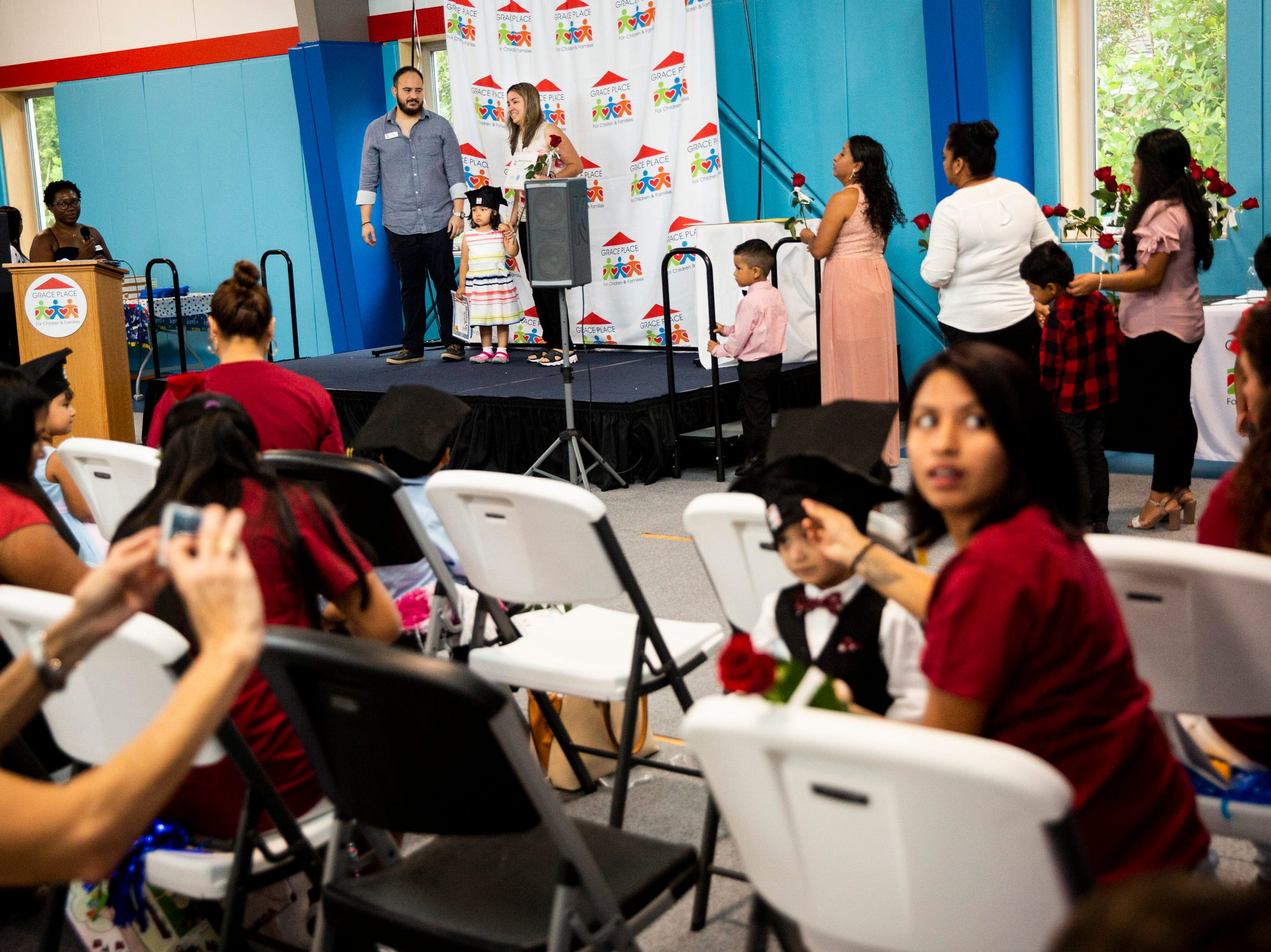 Women line up with their children to receive their graduation certificates during the Bright Beginnings family literacy program graduation at Grace Place in Golden Gate on Wednesday, May 15, 2019.