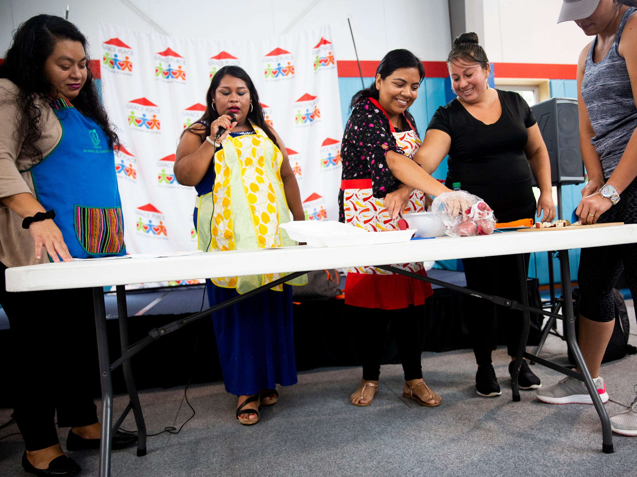 Women from the Bright Beginnings family literacy program perform a skit during their graduation at Grace Place in Golden Gate on Wednesday, May 15, 2019.