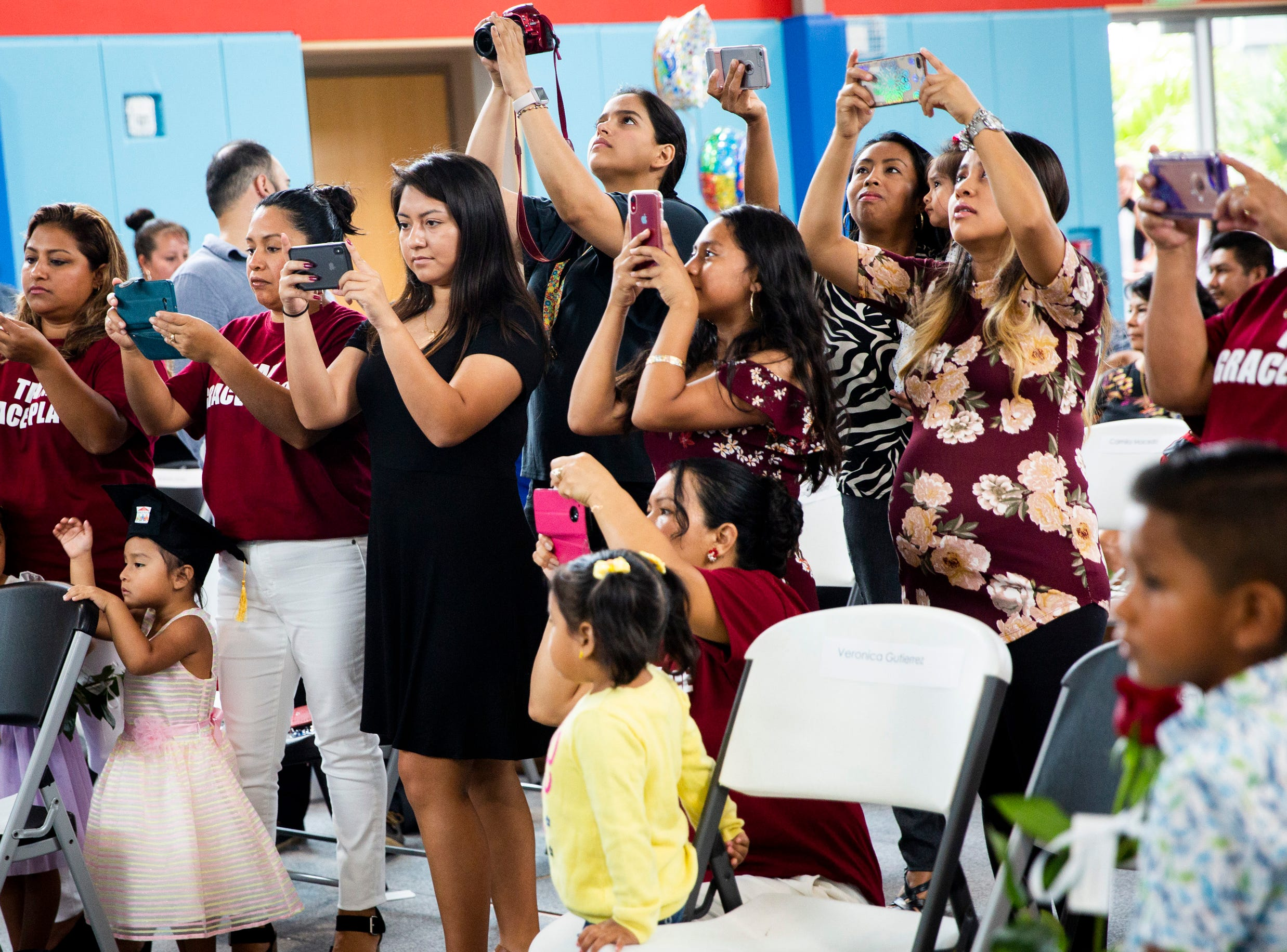 Women take photos of their friends and family during the Bright Beginnings family literacy program graduation at Grace Place in Golden Gate on Wednesday, May 15, 2019.