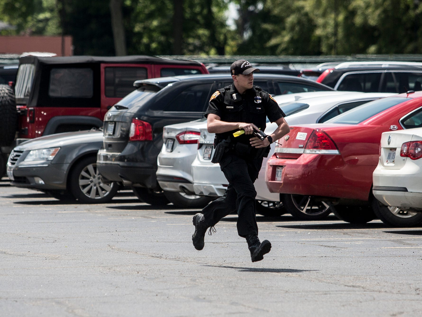 A Newark police office runs into Newark Catholic High School during an active trainer drill Wednesday.