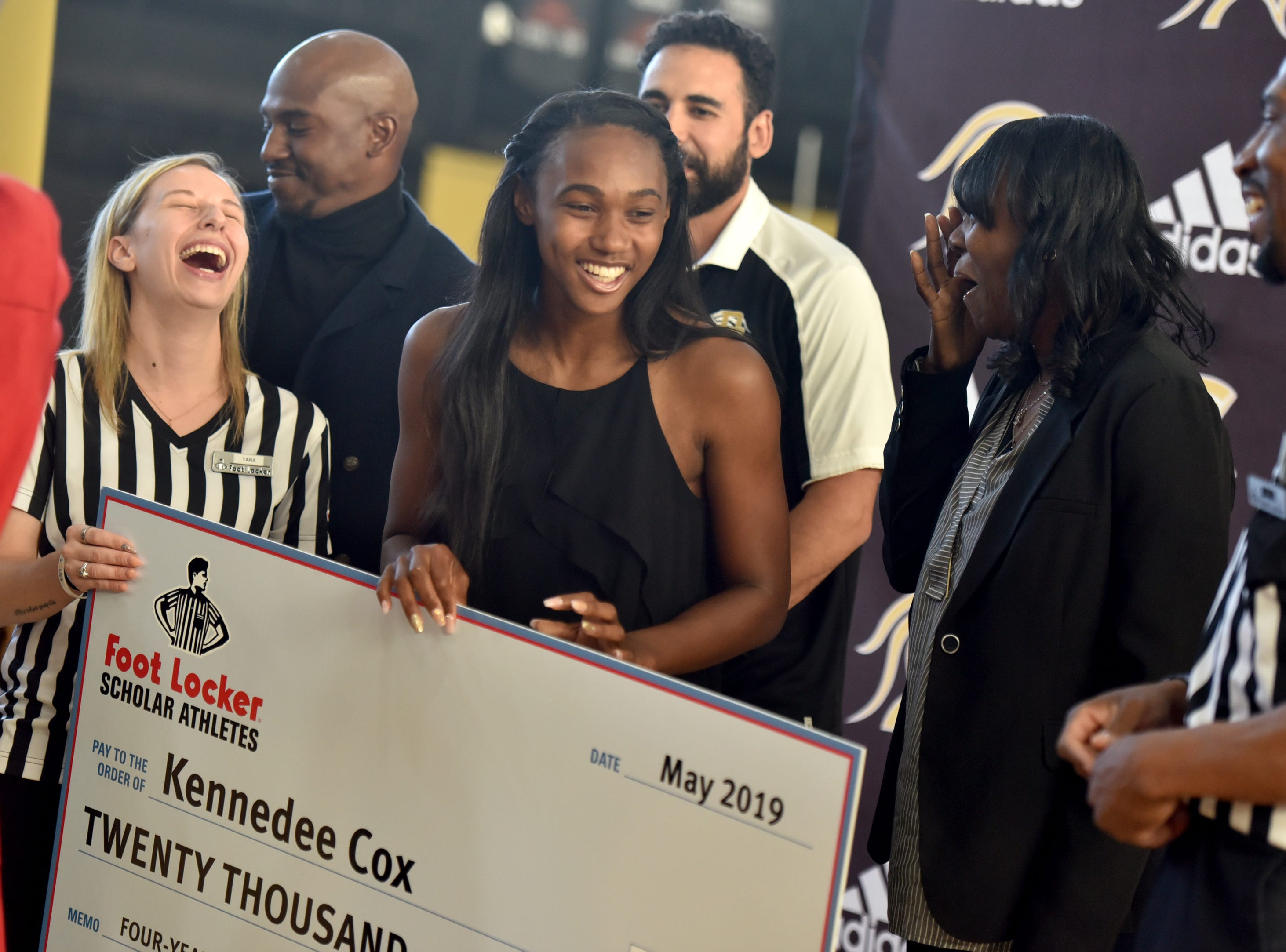 Tara Swett of Foot Locker, Paramus Catholic track coaches Brian Walker and Bryan Durango, Paramus Catholic senior Kennedee Cox and her mother Beverlee Garvin with Cox's $20,000 check from the Foot Locker Scholar Athletes Program. Foot Locker representatives surprised Cox with the announcement at school on Wednesday, May 15, 2019.