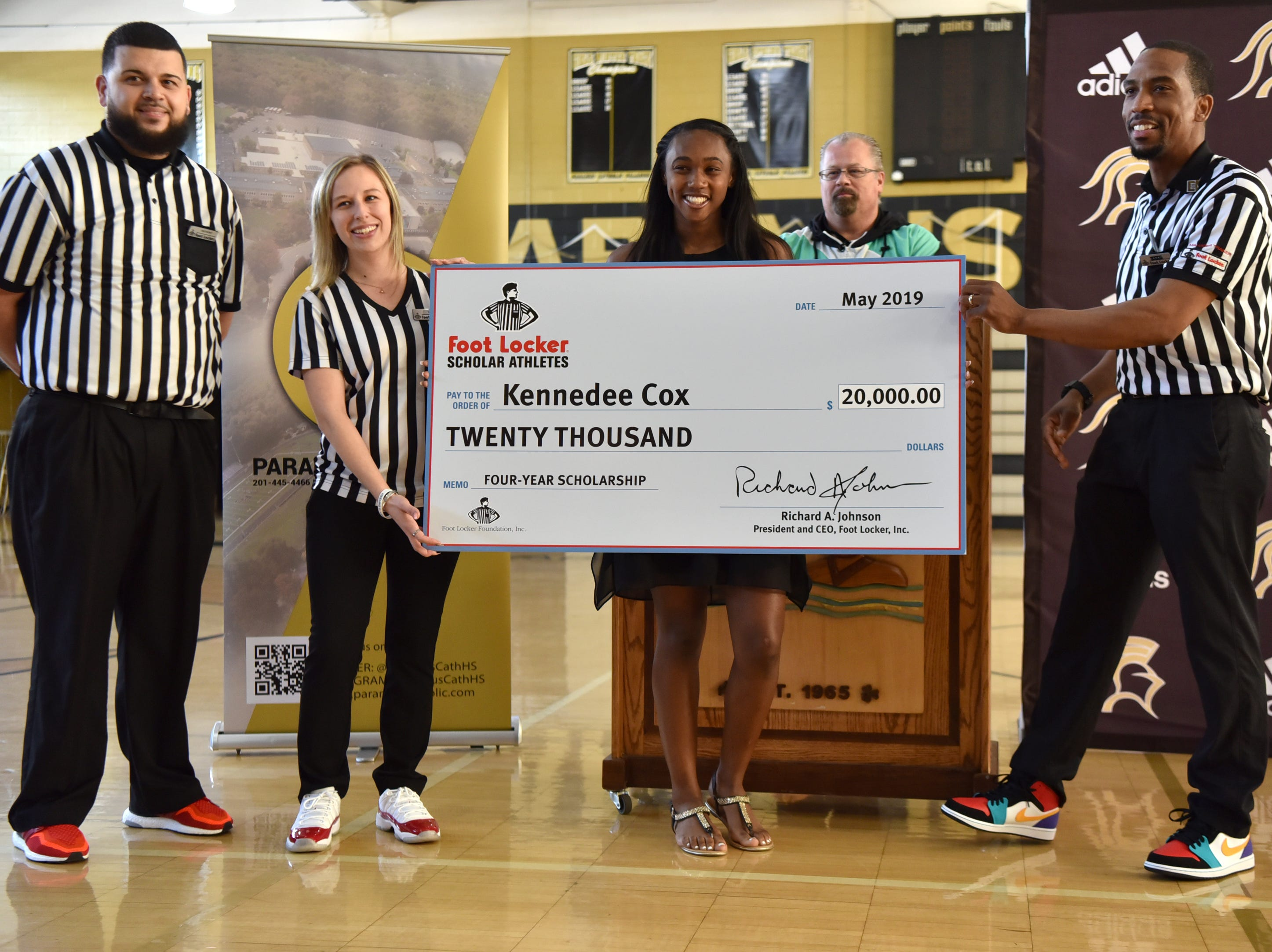 Paramus Catholic senior Kennedee Cox poses for a picture with  $20,000 check from the Foot Locker Scholar Athletes Program. Cox, of Teaneck, runs track at Paramus Catholic. Foot Locker representatives surprised Cox with the announcement at school on Wednesday, May 15, 2019.
