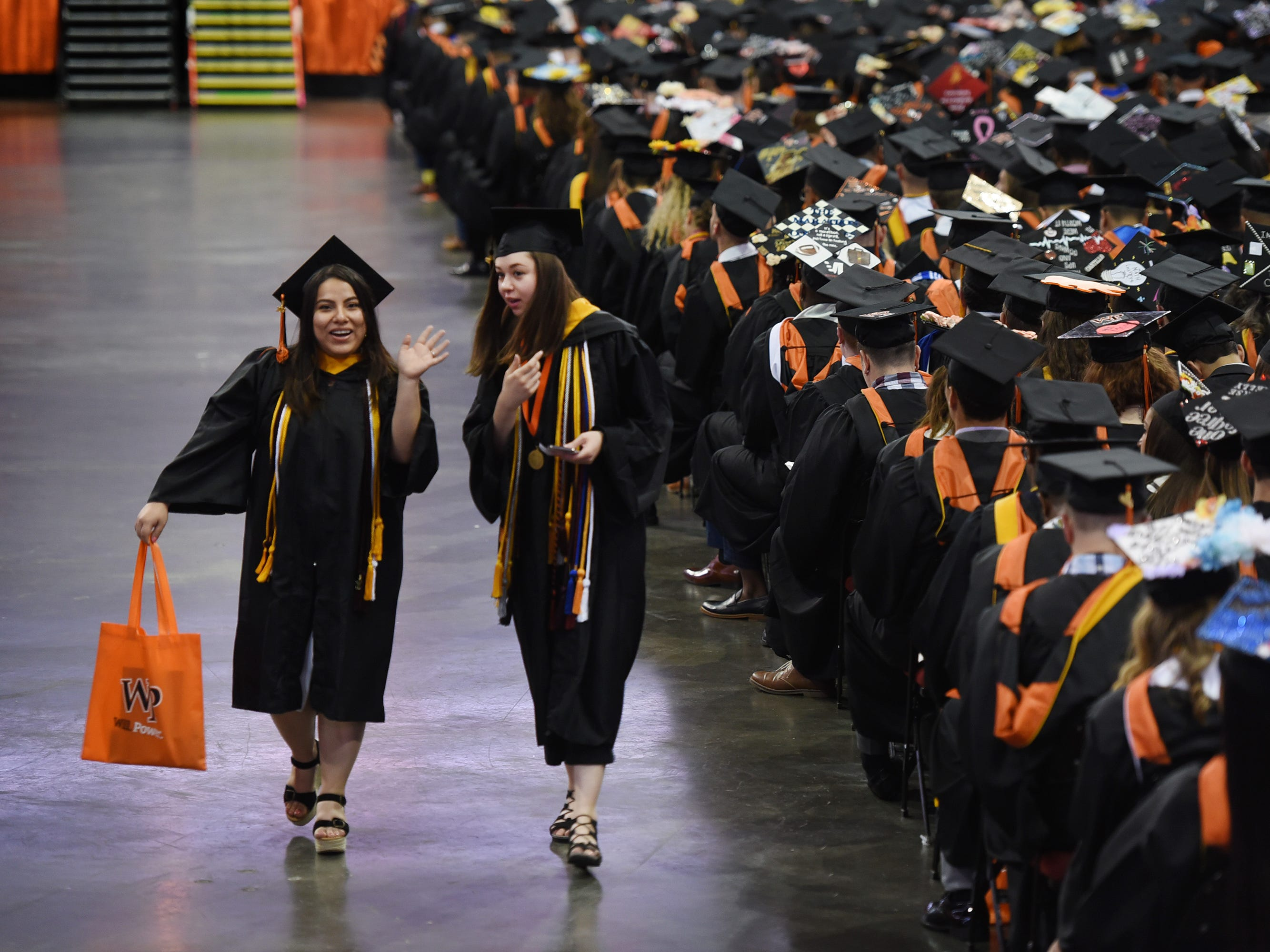 Ana Carysa Salazar (L) of Clifton and Sara Marianna Hope Steinel (R) of Parsippany, both Computer Science Majors, step out from the line during the William Paterson University 2019 Commencement at the Prudential Center in Newark on 05/15/19.