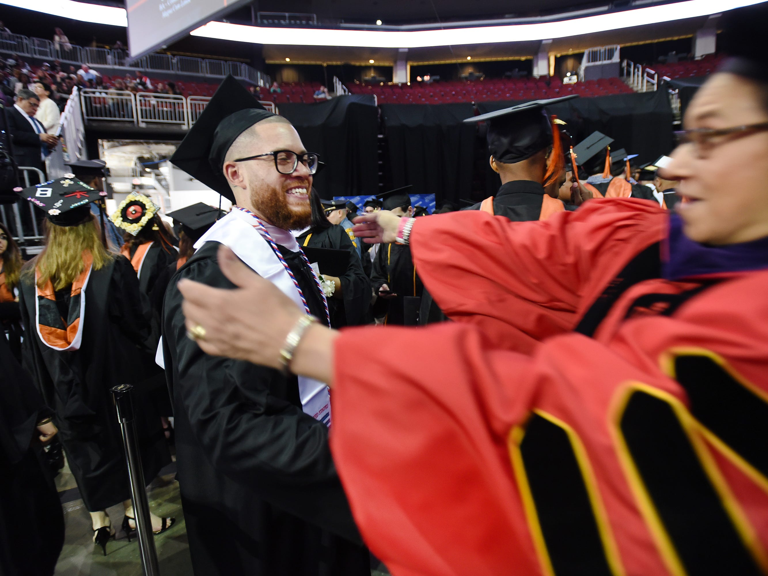 Jacob Martínez, a graduate of William Paterson University, embraces Loretta McLaughlin-Vignier, associate dean of the university's College of the Arts and Communication, at its commencement ceremony on May 15.