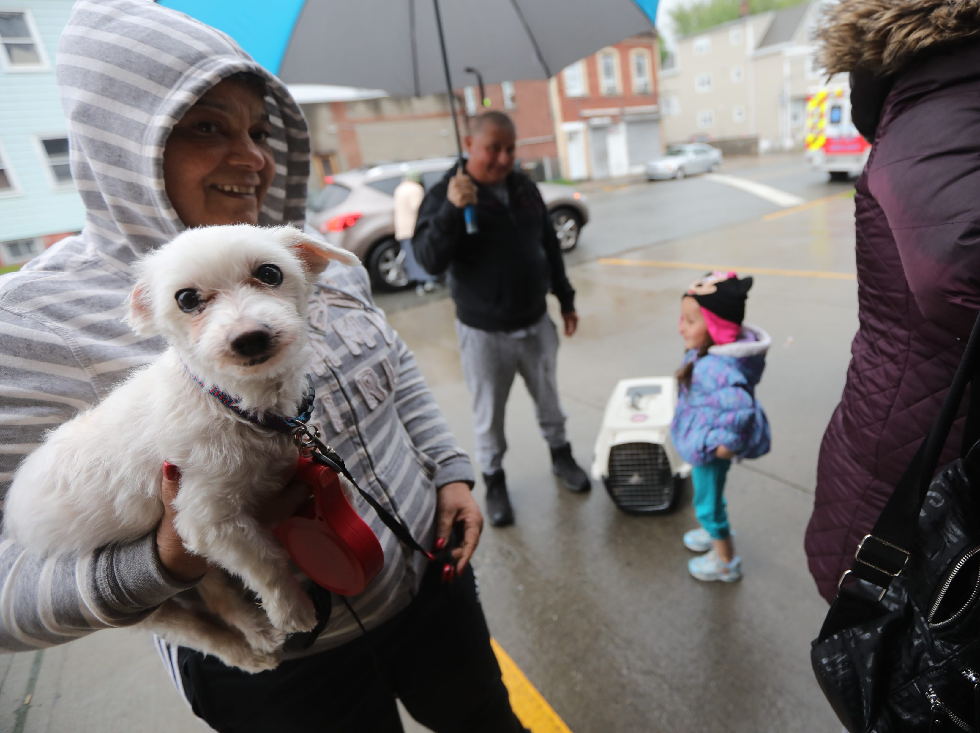 Ana Santiago, holds Doche, while on line to get him vaccinated. People came out to the Riverside Firehouse in Paterson, Tuesday, May 14, 2019, to get free rabies vaccinations for their cats and dogs.  The 44th annual clinic continues Thursday at 128 Getty Ave. and Friday at 300 McBride Ave. from 7-8pm.  It concludes over the weekend, Saturday from 12:30-1:30pm at Firehouse No.4 on Temple St.  Sunday it is back at Riverhouse Firehouse at East 16th St. and Lafayette from 10:30 until noon.